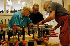 Birgit, Johan och Kenta limmar en möbel som skall vara med på utställningen.